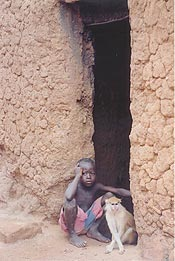 A boy sits pensively with his monkey in one Peace Corps volunteer's village