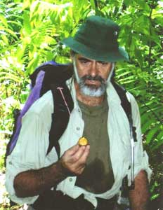 Andy Whitwell, a.k.a. The Pathmaster, examines a seed pod in the rainforest.