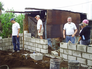Volunteers working with From Houses to Homes in Guatemala building a brick house in the country.