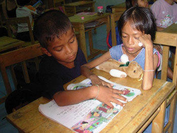 Pim helping one of the younger children to read