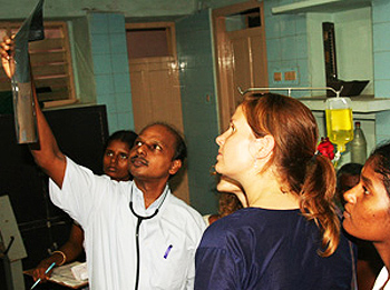 Volunteers and doctor examine x-rays in India.