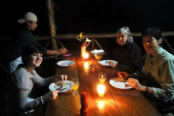 Dinner of volunteers, by candlelight.
