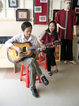 Center founder Miss Nga, right, with a blind musician.