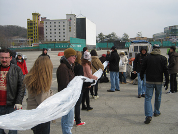 Volunteers help spread out the giant plastic balloon and its payload of socks.