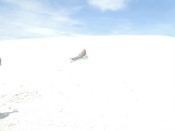 Steffi sledding down the white sand dunes