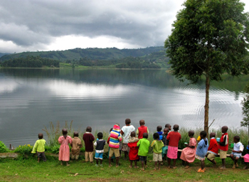 Primary school children eat a breakfast of plain porridge while looking out over the waters of Lake Bunyoni.