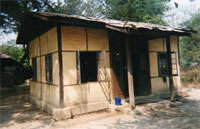 Traditional Burmese village hut, made of bamboo and unfinished teakwood, atop a concrete slab.