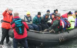 A Zodiac boat filled with eager explorers is pulled up onto the beach of Deception Island.