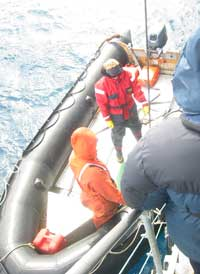 A traveler works his way down the gangway and onto the Zodiac boat below.