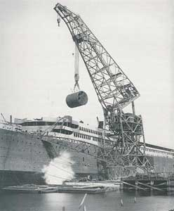 A floating crane loads a boiler into the Titanic during its construction in Belfast.