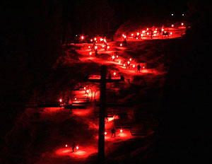 A parade of skiers with torches resembles a flow of red hot lava