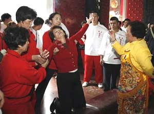 A woman goes into an ecstatic trance at the Tienhou Temple.
