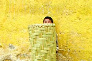 A Mayan youngster hides behind a market basket.