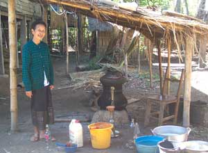 A Lao woman offering samples of her lao khao (rice whiskey)