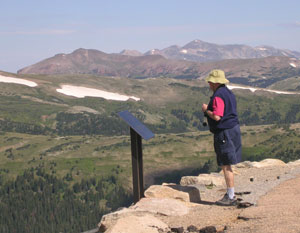 A tourist gazes at the view atop Rocky Mountain National Park.