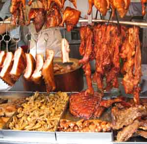 Roast pork, beef and chicken pieces hanging in a shop window in Macau.