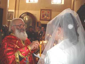 A Georgian priest 'crowns' a new bride.