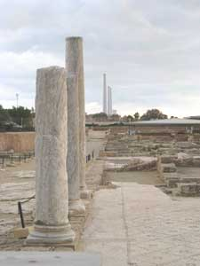 Ancient Roman pillars and a modern electrical plant in the distance