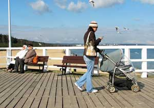 Local people making best of morning sunbeams on a cold March day on the Sopot Pier.