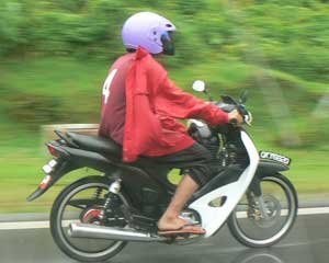 A motorcyclist braves the rain in Kuching