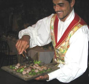 Server with a platter of myrtle covered sausage