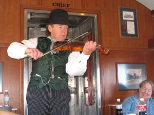 A fiddler performs on the GraWandering minstrels entertain the passengers. Don't forget to tip!