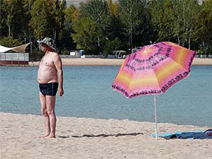 Vacationers sunbathe standing up on the beach at Issyk Kul.