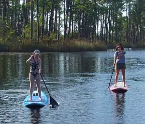 Yolo boarders paddle their way around Western Lake at WaterColor Inn and Resort.
