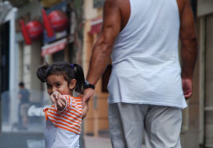 Little girl waving to a street vendor on the walking street (peatonal) Sarandi