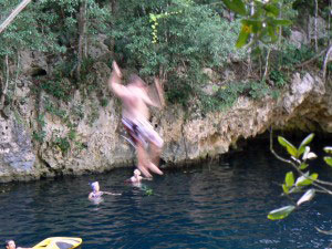 Jumping into the blue water of the cenote, at Selvatica, in Mexico