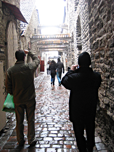 A couple hurries down St. Catherine's Passage, one of the most picturesque place in Tallinn