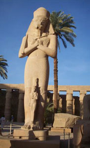 An imposing granite statue of the great pharaoh Ramses II, with one of his daughters at his feet, guards the entrance to the Hypostyle Hall.