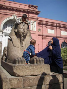 Egyptian children play atop a replica of The Great Sphinx at the entrance to the Egyptian Museum, permanent home of the King Tut Exhibit.
