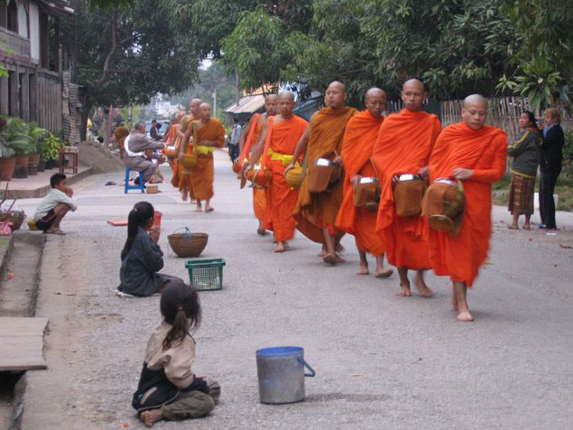 Children give offerings of food to the monks in Luang Prabang.