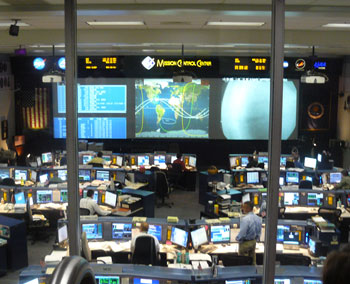 Mission Control at the Johnson Space Center in Houston. The curved lines on the screen track the orbits of the Space Shuttle.
