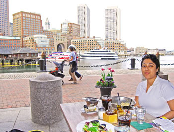 Esha at The Daily Catch with the Boston skyline in the background.