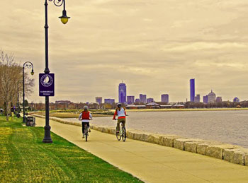 Bikers along Dorchester Bay. The Boston Harborwalk sign-board in the forefront with the Boston skyline in the distance.