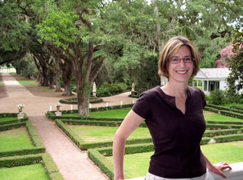 The author poses on the second-story porch of the Rosedown Plantation home with the front gardens in the background.