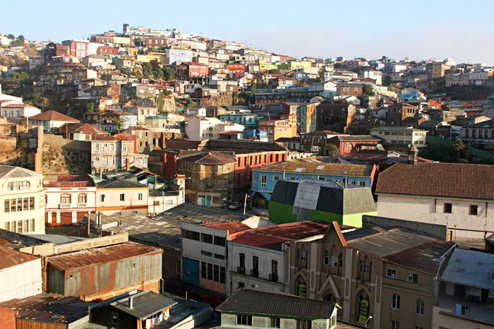 Ramshackle houses and colonial architecture fight for space on the steep hillside of Cerro Cordillera in Valparaiso, Chile.