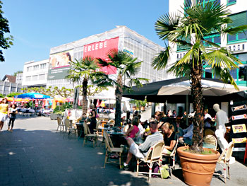 Main street Vaduz crowded with people spending the beautiful day outdoors dining