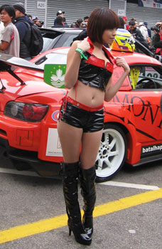 An umbrella girl poses on the pit lane.