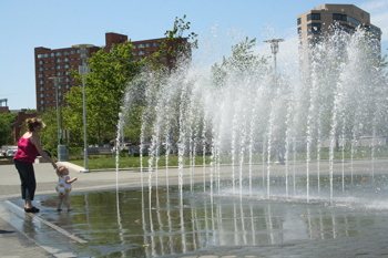 A mother and daughter play in the fountains by the Baltimore Visitor Center. Photo by Emily Grund.