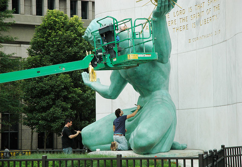 A statue by Marshall Fredericks titled 'The Spirit of Detroit' gets a washing by city workers. Photo by Lisa Singh