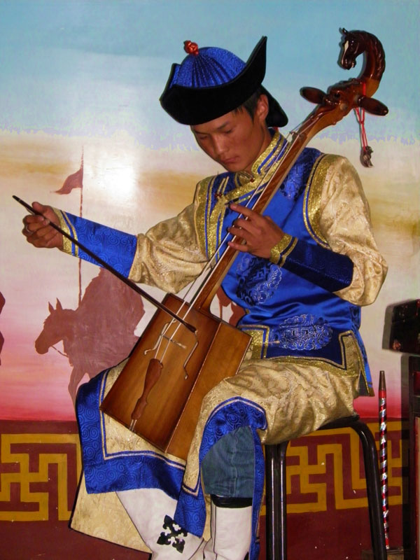 Playing a two-stringed horsehair fiddle in Shangtu, Mongolia