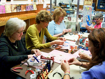 Beaders wrap sea glass pendants in copper wire attentively during a class held by Christi Bartos at All About Beads.
