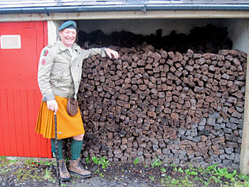 Brendan Rohan poses next to piles of peat at The Corcreggan Mill in Dunfanaghy, where he owns and operates a hostel and B&B.