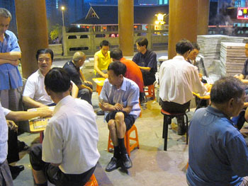 Men gather to play Mahjong on a warm summer evening in Enshi.