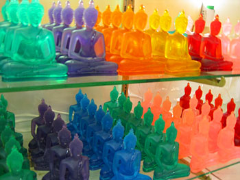 Multi-colored glass Buddhas adorn a shelf at Chatuchak Market.