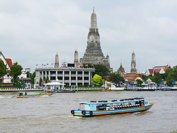 A river taxi plies the Chao Phraya River in front of Wat Arun.