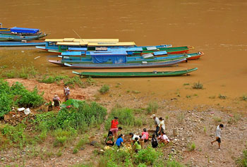 Locals sell food by the riverside.